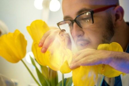 handsome scientist in glasses grew a sexy girl in the yellow blooming flower