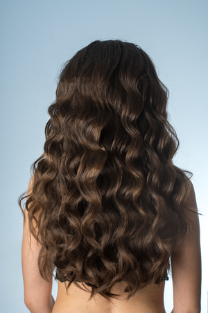 girl with long curly hair in studio on grey background