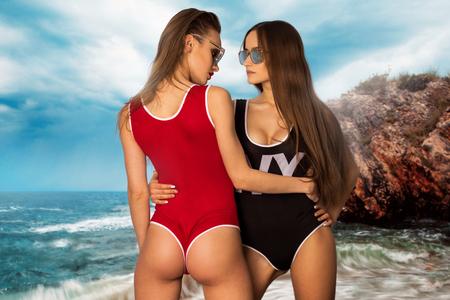 Dos chicas calientes posando en la playa en traje de baño corporal
