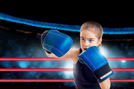 Young sports girl in boxing ring shots a punch Stock Photo