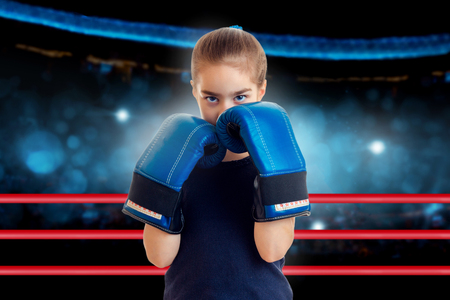 Little sports girl in boxing ring ready for the fight