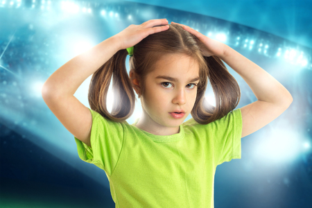 portrait of cute little girl with pigtails in green football shirt looking at the camera at football stadium