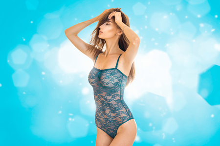 sensual young brunette girl in blue body lace underwear with closed eyes 写真素材