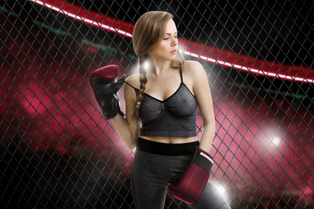 Slim blonde girl mma fighter in red gloves looking away inside the cage Stockfoto
