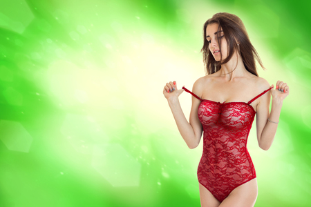 Sensual young girl take off a red body underwear in studio on green background
