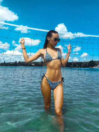 slim young brunette in stripes swimsuit and sunglasses stands in the blue sea in the summer time