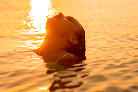 young sexual lady in the sea at warm sunset Stock Photo