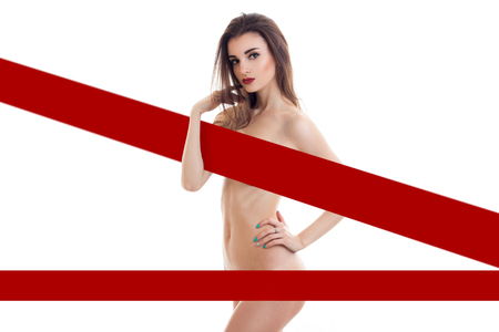 Gorgeous young lady with sexy body hides behind the red stripes isolated on white background Stock Photo