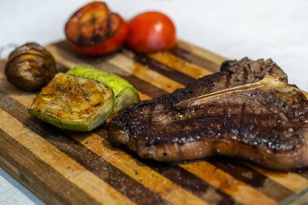 mouthwatering beef t-bone steak and grilled vegetables Imagens