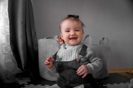 Cutie little baby girl smiles on camera at home