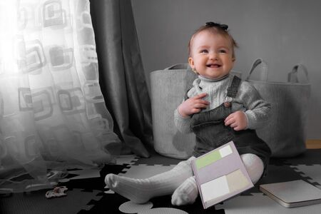 Funny little baby girl smiles at home