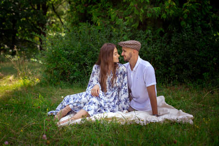 beautiful couple in love at the picnic smiles each others at the green nature