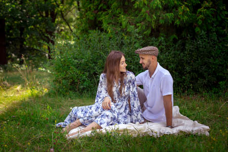 pretty couple in love at the picnic smiles each others at the green nature