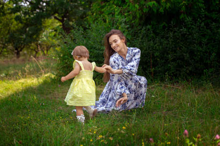 happy stylish young mother plays with her little daughter at the green garden Stock Photo