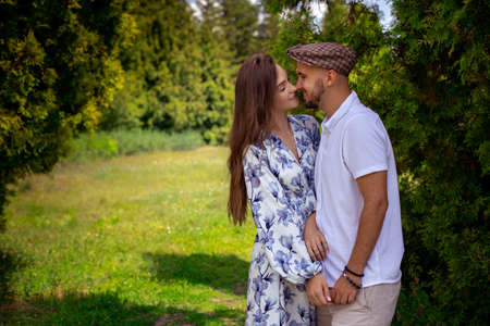 horizontal portrait of charming couple in love hugs and holds hands at the green garden