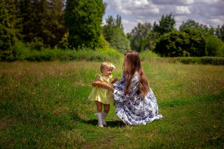 Cheerful young mother plays with her little daughter at the green meadow