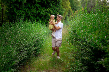 stylish young caucasian father walks carrying little daughter at the garden