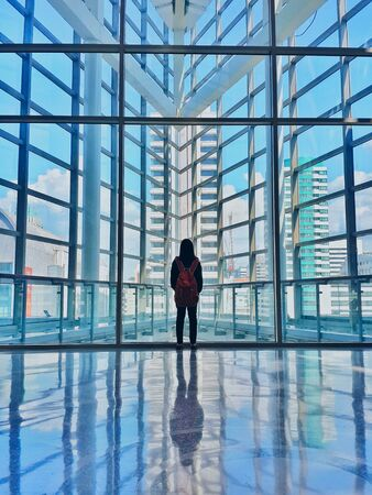 grid: Girl standing in a modern building