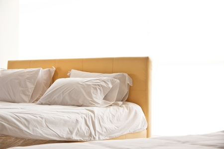 bedding indoors: modern white bed and pillow in the morning mood