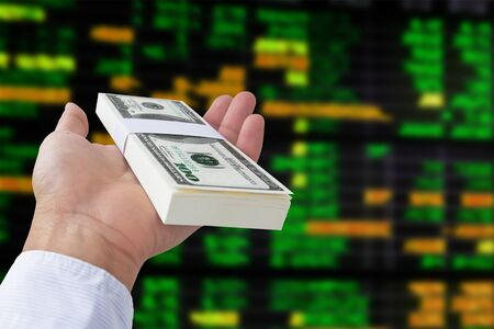money in hand on stock exchange board background  photo