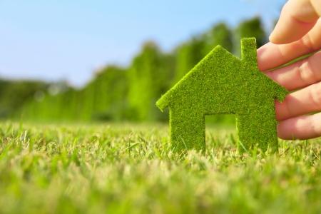 medio ambiente: mano que sostiene Eco House icono en la naturaleza Foto de archivo