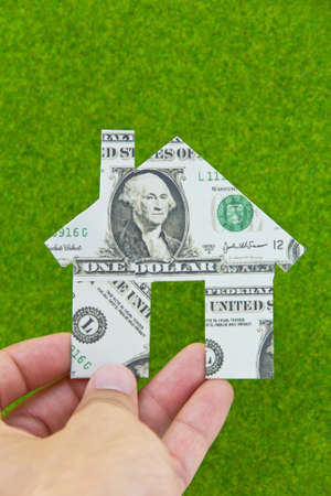 Hand holding banknote house icon photo