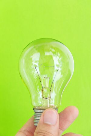 light blub in hand with green background, eco energy concept photo