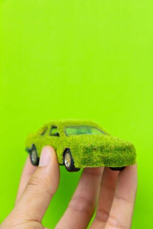 Hand Holding Eco car icon isolate on green background photo