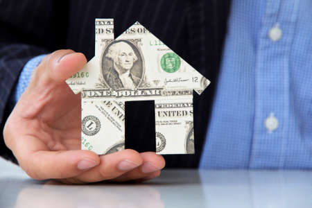 business man holding banknote house icon photo