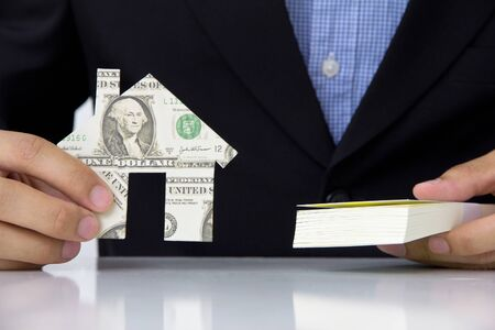 hand holding banknote house icon, real estate concept  photo
