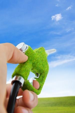 bomba de gasolina: mano eco celebraci�n de la boquilla de combustible, concepto de energ�a