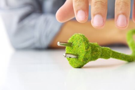 electric plug: hand holding eco electric plug Stock Photo