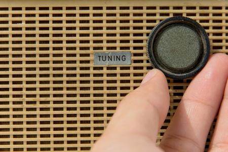 tuning: hand adjust vintage radio tuning knob concept