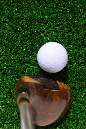 Golf ball and driver on green grass background  photo