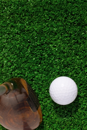 Golf ball and putter on green grass background  photo