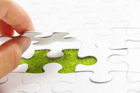 hand die een stukje van de puzzel, groene ruimte concept