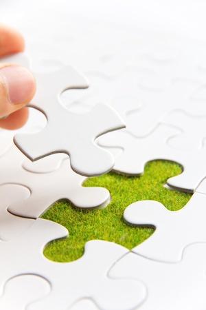 Hand insluiten ontbrekende puzzelstukje op zijn plaats, groene ruimte concept
