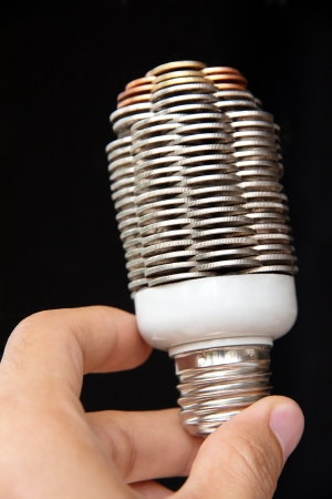 overuse: hand holding coin light bulb concept