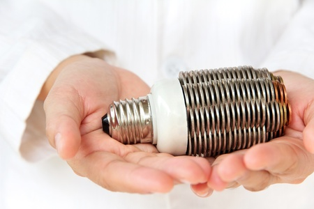 overuse: hand holding coin light bulb concept