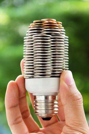 save earth: hand holding coin light bulb,energy concept