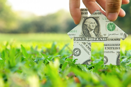 dream home: Hand holding banknote house icon,real estate concept