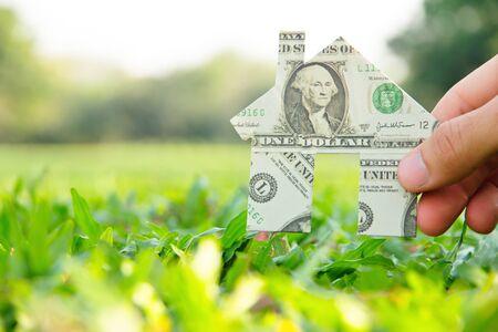 Hand houden bankbiljet huispictogram, onroerend goed concept Stockfoto