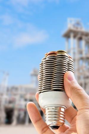 hand holding coin light bulb,energy concept  photo