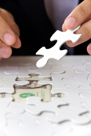 creative money: business man hand holding a puzzle piece, money concept