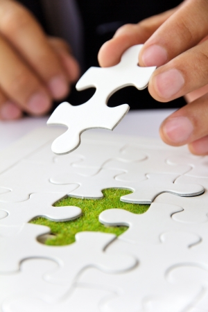 business man hand holding a puzzle piece, green space concept 版權商用圖片