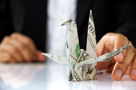 find solution: business man hand holding origami paper cranes, money concept Stock Photo