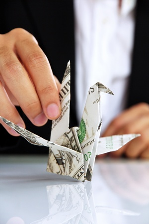 business man hand holding origami paper cranes, money concept photo
