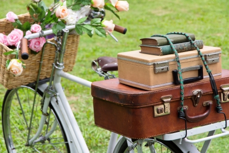Vintage bicycle on the field with a basket of flowers and bag Imagens
