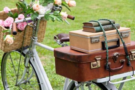 vintage: Vintage cykel på fältet med en korg av blommor och väska Stockfoto