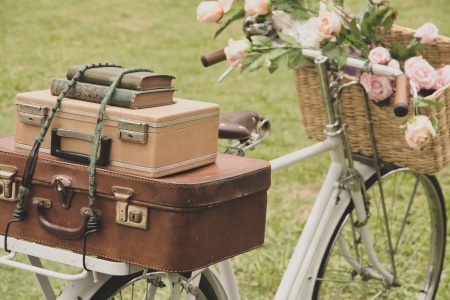 Vintage bicycle on the field with a basket of flowers and bag Stock Photo